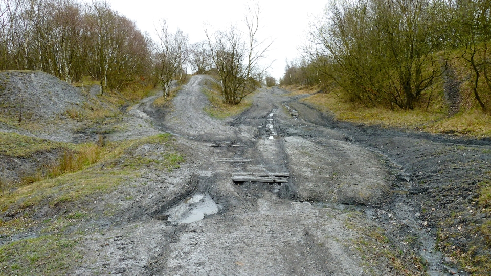 View looking back towards the pretty high slag heap on the left and and old track bed with a few broken sleepers showing through in the foreground.